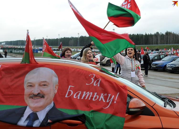 Девушки машут флагами на фоне автомобиля с изображением Александра Лукашенко на провластном автопробеге. Аэродром Липки, Минск, 8 ноября 2020 года.